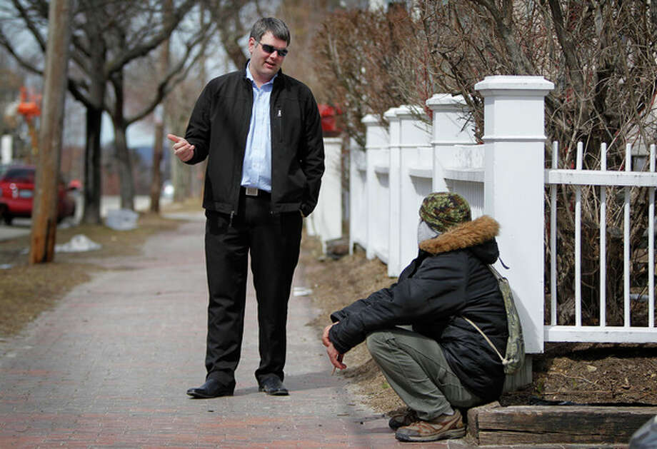 In this March 24, 2013 photo, former Marine Corps Cpl. Marshall Archer, left, a veterans' liaison for the city of Portland, Maine, speaks to a man on a street in Portland. Veterans groups are rallying to fight any proposal to change disability payments as the federal government attempts to address its long-term debt problem. They say they've sacrificed already. (AP Photo/Robert F. Bukaty) / AP