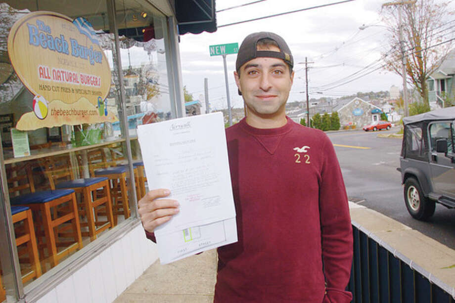 Anthony Luciani owner of Beach Burger at 10 First St., and Frosty's Ice Cream at 6 First St. with his new seating certificate. The ongoing battled between owners of Harbor Lights at 82 Seaview Ave./Overton's and Beach Burger that is over parking is really about competition. Hour photo / Erik Trautmann / (C)2011, The Hour Newspapers, all rights reserved