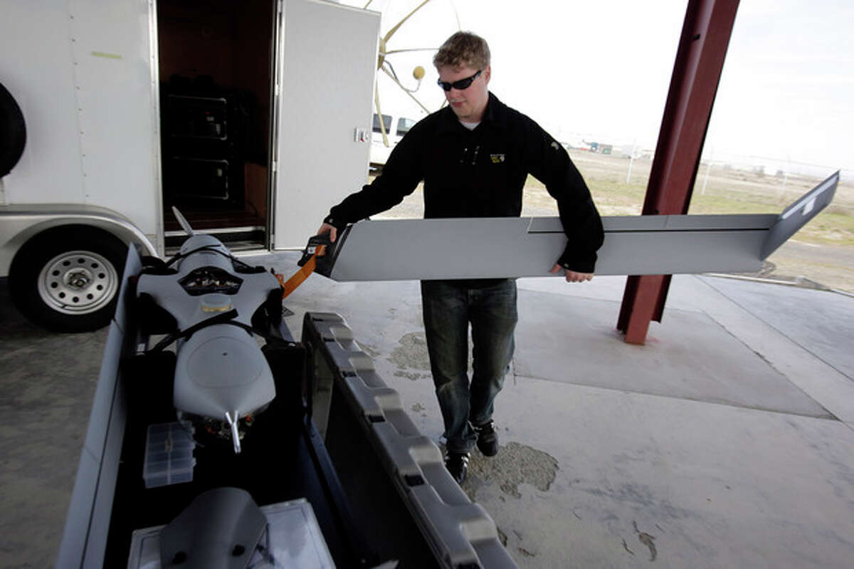 This photo taken March 26, 2013, shows flight test pilot Alex Gustafson dismantling a Insitu ScanEagle unmanned aircraft after a flight in Arlington, Ore. It?'s a good bet that in the not-so-distant future aerial drones will be part of Americans?' everyday lives, performing countless useful functions. A far cry from the killing machines whose missiles incinerate terrorists, these generally small unmanned aircraft will help farmers more precisely apply water and pesticides to crops, saving money and reducing environmental impacts. They?'ll help police departments to find missing people, reconstruct traffic accidents and act as lookouts for SWAT teams. They?'ll alert authorities to people stranded on rooftops by hurricanes, and monitor evacuation flows. (AP Photo/Don Ryan)