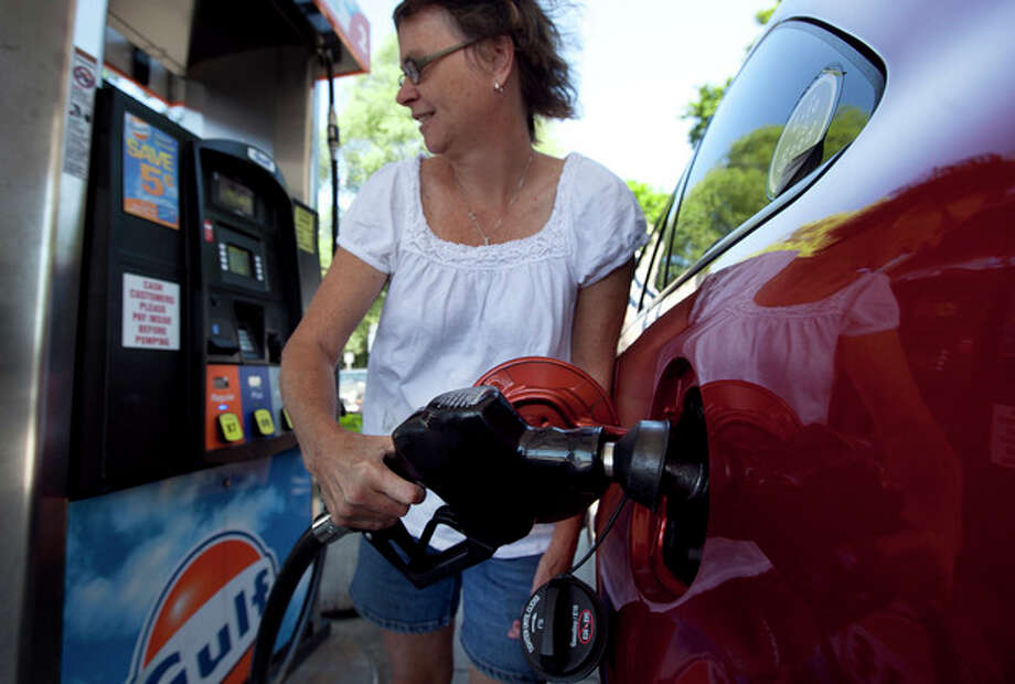FILE - In this July 10, 2012 file photo, Suzanne Meredith, of Walpole, Mass., gases up her car at a Gulf station in Brookline, Mass. Reducing sulfur in gasoline and tightening emissions standards on cars beginning in 2017, as the Obama administration is proposing, would come with costs as well as rewards. (AP Photo/Steven Senne, File) / AP