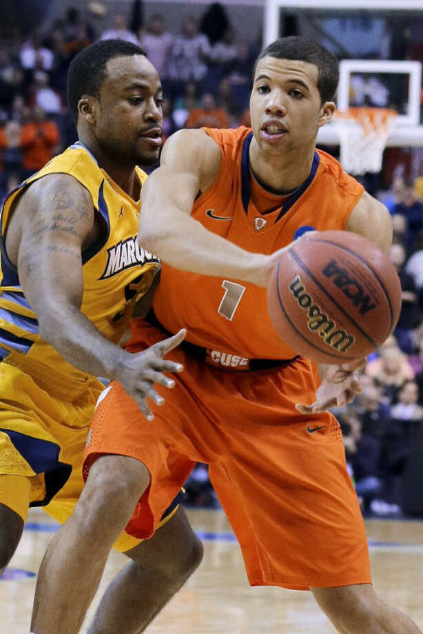Syracuse guard Michael Carter-Williams (1) passes around Marquette guard Junior Cadougan during the first half of the East Regional final in the NCAA men's college basketball tournament, Saturday, March 30, 2013, in Washington. (AP Photo/Alex Brandon)