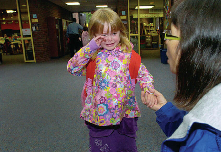 Miller Driscoll School kindergartner Grace Dibuono-Krafick gets a helping hand from special education para-professional Lisa Neucheler on the first day of school Tuesday. / (C)2011, The Hour Newspapers, all rights reserved