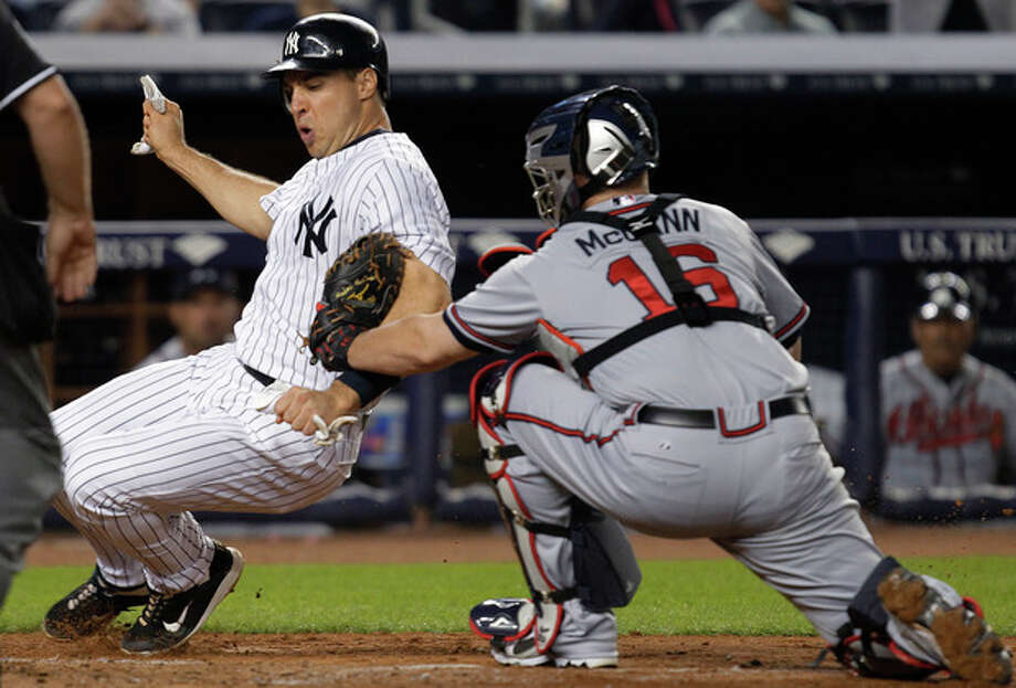 Atlanta Braves catcher Brian McCann (16) tags out New York Yankees' Mark Teixeira during the fifth inning of a baseball game at Yankee Stadium in New York, Tuesday, June 19, 2012. (AP Photo/Kathy Willens) / AP