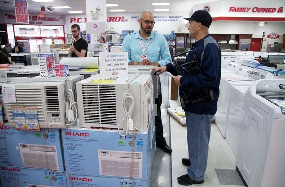 Salesman Carlos Burgos, center, helps customer Raven Campbell, right, select an air conditioner at P.C. Richard & Son, an electronics and appliance store, Tuesday, June 19, 2012 in the Brooklyn borough of New York. Temperatures are expected to approach or top 100 degrees Wednesday and Thursday in cities including New York, Philadelphia and Boston. (AP Photo/Mark Lennihan) / AP