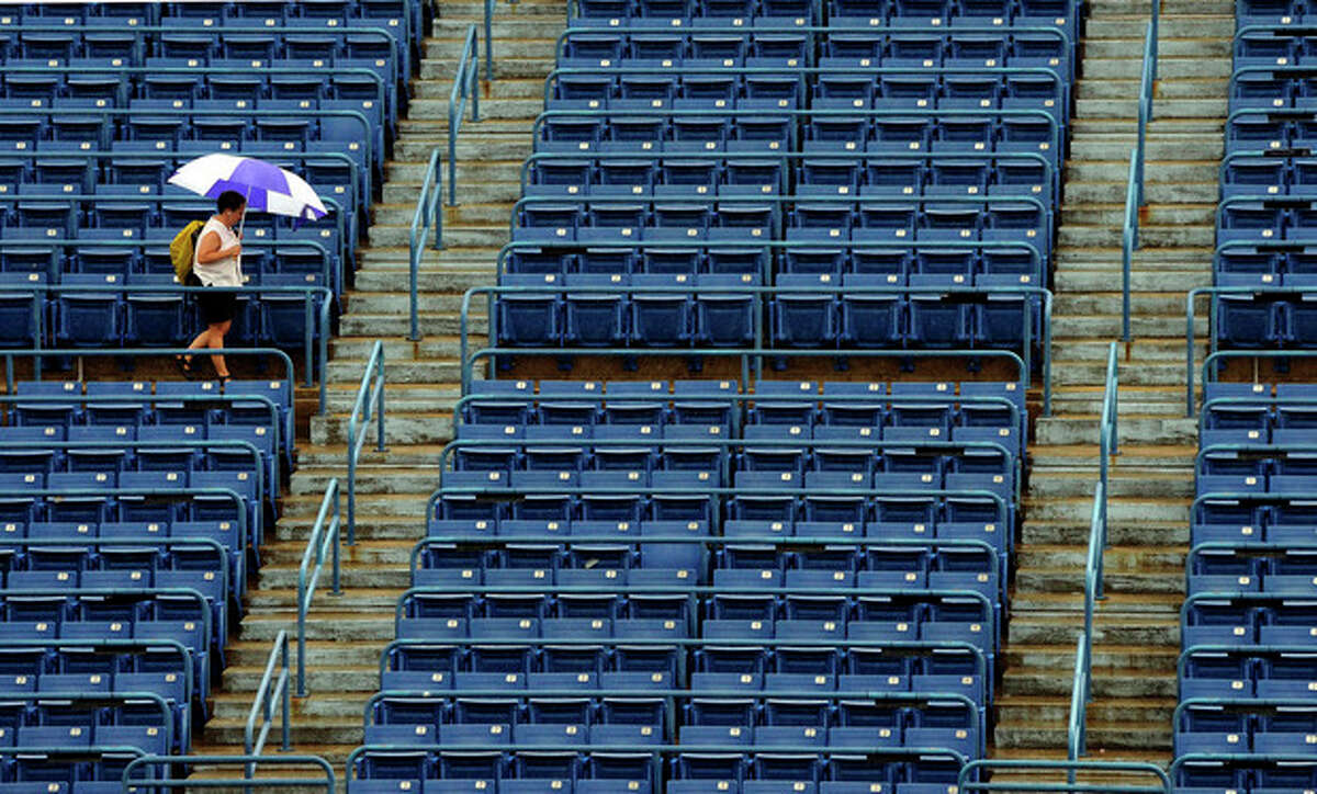 A spectator leaves the stadium court during a rain delay at the New Haven Open tennis tournament in New Haven, Conn., on Thursday, Aug. 25, 2011. (AP Photo/Fred Beckham)