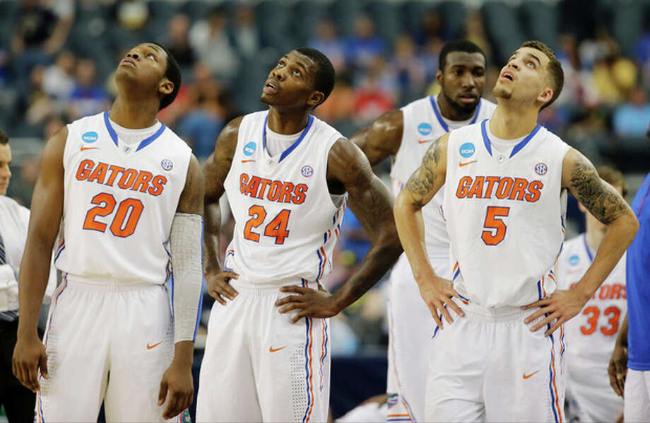 Florida players Michael Frazier II (20), Casey Prather (24) and Scottie Wilbekin (5) watch the big screen during the first half of a regional final game against Michigan in the NCAA college basketball tournament, Sunday, March 31, 2013, in Arlington, Texas. (AP Photo/David J. Phillip) / AP