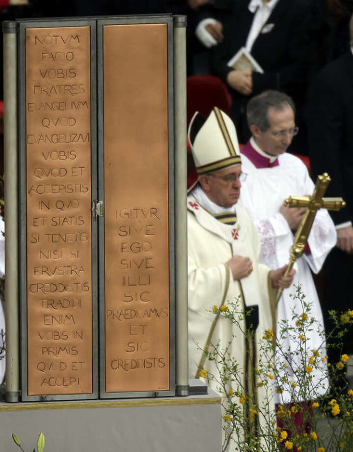 """Pope Francis, holding the pastoral staff, walks past the closed icon of Jesus as he celebrates the Easter mass in St. Peter's Square at the Vatican, Sunday, March 31, 2013. """"Our daily problems and worries can wrap us up in ourselves, in sadness and bitterness, and that is where death is,"""" he said. """"Let the risen Jesus enter your life, welcome him as a friend, with trust: he is life!"""" said Pope Francis during the Easter vigil. (AP Photo/Gregorio Borgia)"""