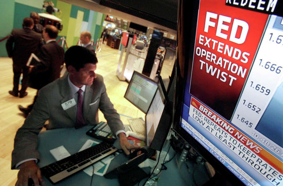 The decision of the Federal Reserve is visible on a television monitor at the trading post of specialist Michael Guli, on the floor of the New York Stock Exchange Wednesday, June 20, 2012. The Federal Reserve is extending a program designed to drive down long-term interest rates to spur borrowing and spending. (AP Photo/Richard Drew) / AP