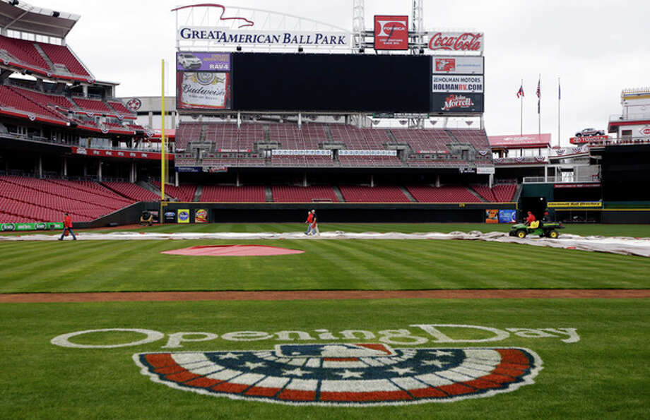 Cincinnati Reds grounds crew members prepare the field ready at Great American Ball Park for Monday's opening day baseball game against the Los Angeles Angels, Sunday, March 31, 2013, in Cincinnati. (AP Photo/Al Behrman) / AP
