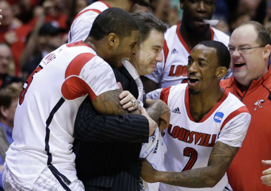 Louisville head coach Rick Pitino celebrates with Chane Behanan, left, and guard Russ Smith (2) after their 85-63 win over Duke in the Midwest Regional final in the NCAA college basketball tournament, Sunday, March 31, 2013, in Indianapolis. (AP Photo/Darron Cummings) / AP