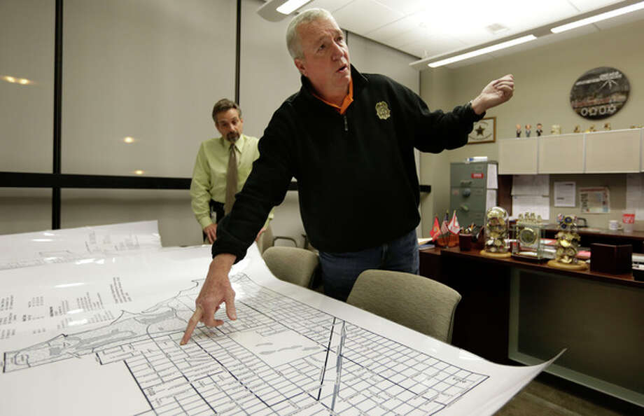 In this Dec. 11, 2012 file photo, Jack Riley, head of the Drug Enforcement Administration in Chicago, points out local Mexican drug cartel problem areas on a map in the new interagency Strike Force office in Chicago. Looking on is DEA agent Vince Balbo. The ruthless syndicates have long been the nation's No. 1 supplier of illegal drugs, but in the past, their operatives rarely ventured beyond the border. A wide-ranging Associated Press review of federal court cases and government drug-enforcement data, plus interviews with many top law enforcement officials, indicate the groups have begun deploying agents from their inner circles to the U.S. (AP Photo/M. Spencer Green, File) / AP