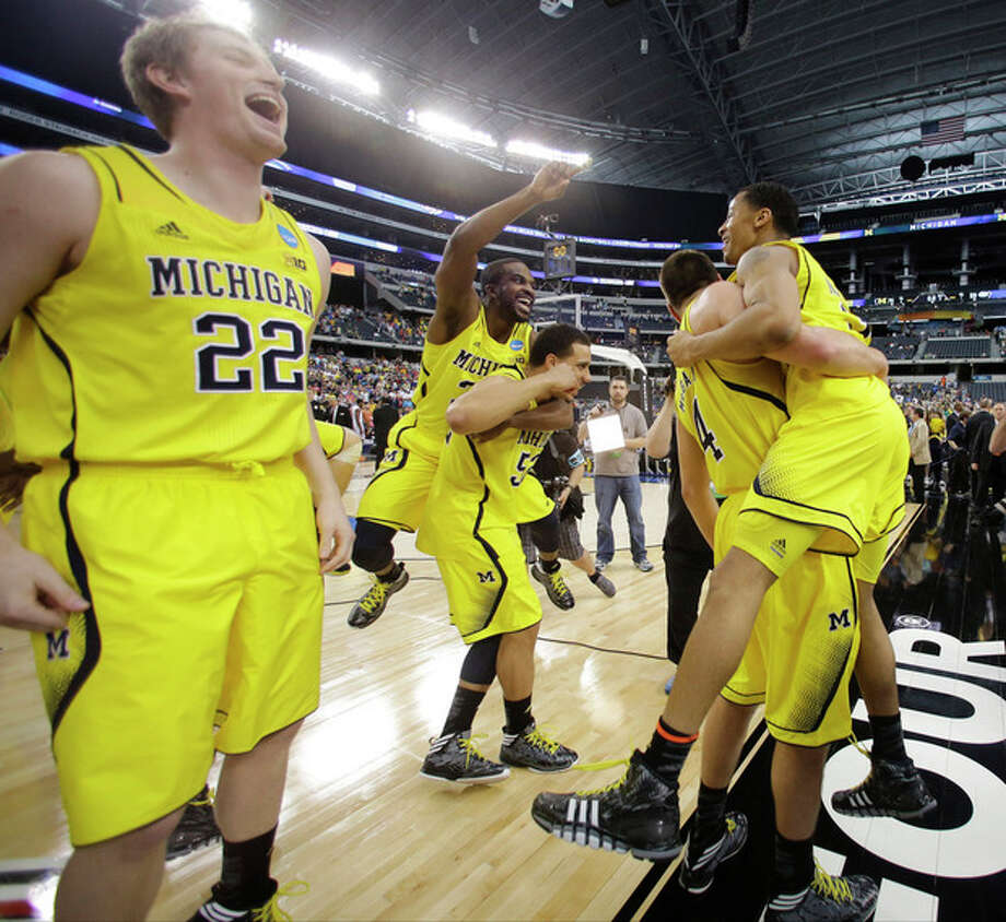 Michigan celebrates after a regional final game against Florida in the NCAA college basketball tournament, Sunday, March 31, 2013, in Arlington, Texas. Michigan won 79-59 to advance to the Final Four. (AP Photo/Tony Gutierrez) / AP