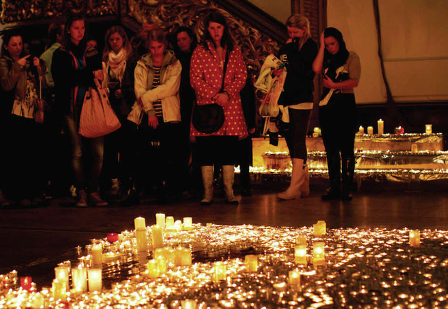 People stand in silent tribute as they look at candles burning in memory of the victims of the attacks on Norway's government headquarters and an island youth retreat, as they pay their respects at Oslo Cathedral, Sunday, July 24, 2011. A Norwegian man detonated a bomb in central Oslo and then gunned down at least 84 people on Friday at Utoya island youth retreat, before being arrested. (AP Photo/Matt Dunham) / AP