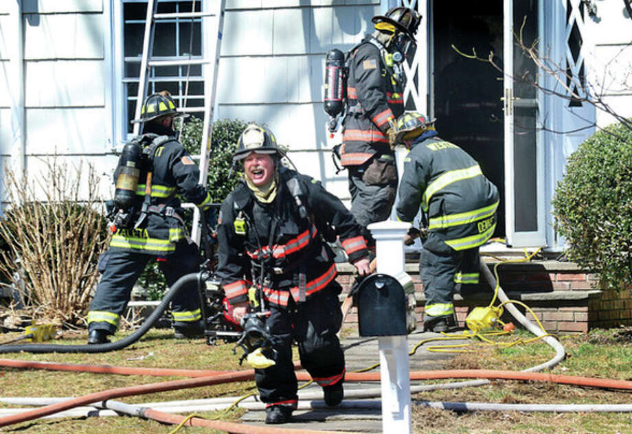Hour photo / Erik TrautmannWestport firefighters battle a blaze that erupted at 10 Pond Ridge Road Wednesday morning. / (C)2013, The Hour Newspapers, all rights reserved