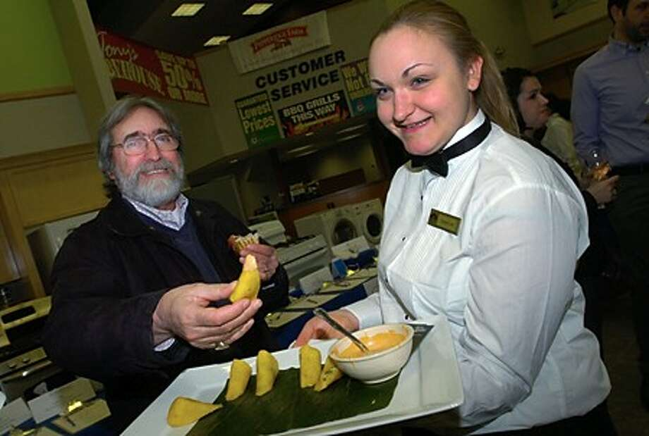 Richard Mintz is served hors d''oerves by Norwalk Commmunity College student Crystal Lord of their Restaurant Management Program during the Norwalk Education Foundation fundraiser, Taste of Education, at Aitoro Appliance Thursday evening. Hour photo / Erik Trautmann