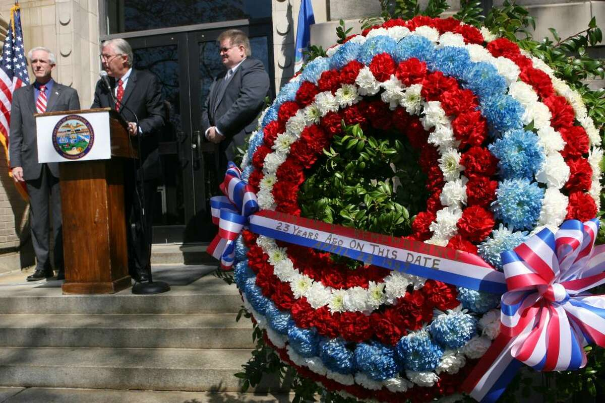 Bridgeport Mayor Bill Finch, left, stands at the podium with Tom Wilkinson, President of the Fairfield Labor Council, center, and Pete Carroll during the 23rd annual memorial ceremony of L'Ambiance Plaza on Friday, April 23, 2010. L'Ambiance Plaza collapsed in 1987 during construction killing 28 construction workers.