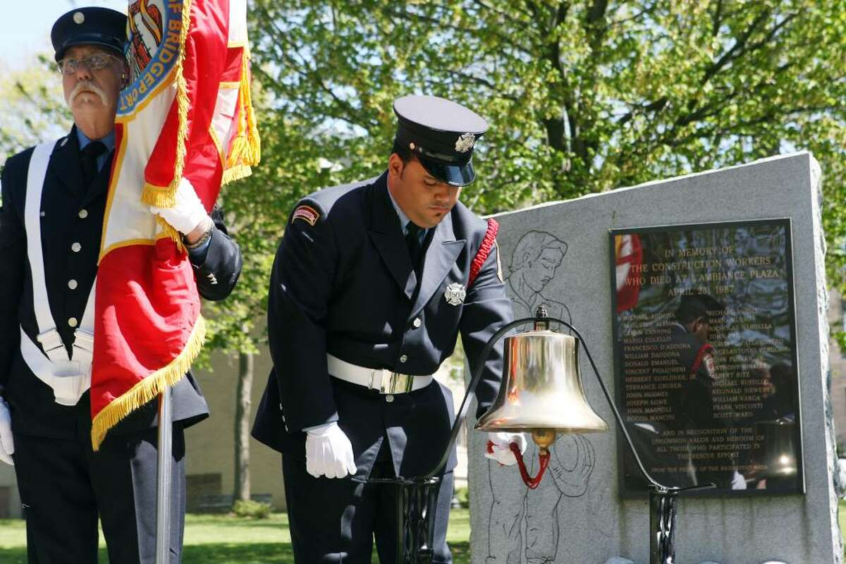 Christopher Vega, of the Bridgeport Fire Department, rings the bell during the 23rd annual memorial ceremony of L'Ambiance Plaza on Friday, April 23, 2010. L'Ambiance Plaza collapsed in 1987 during construction killing 28 construction workers.