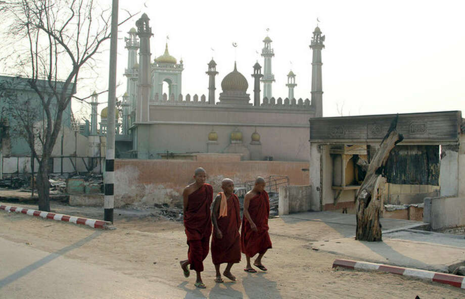 Three Buddhist monks walk on a road near a mosque in Meikhtila, about 550 kilometers (340 miles) north of Yangon, Myanmar, Monday, March 25, 2013. Sectarian clashes between Buddhists and Muslims in Myanmar spread to at least two other towns in the country's heartland over the weekend, undermining government efforts to quash an eruption of violence that has killed dozens of people and displaced 10,000 more. On Sunday, Vijay Nambiar, the U.N. secretary-general's special adviser on Myanmar, toured Meikhtila, where soldiers were able to impose order after several days of anarchy and called on the government to punish those responsible. (AP Photo/Khin Maung Win) / AP