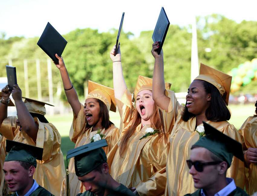 Graduates K-la Rogers, of Seymour, Kirsten Reardon, of Naugatuck, and Adrienne McNeill, of West Haven, from left, hold up their diplomas and cheer during the Emmett O'Brien Technical High School commencement ceremony at Nolan Field in Ansonia, Conn. on Tuesday, June 14, 2016.