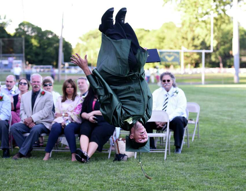 Graduate Charlie Ricco, of Seymour, does a backflip in front of his teachers after accepting his diploma during the Emmett O'Brien Technical High School commencement ceremony at Nolan Field in Ansonia, Conn. on Tuesday, June 14, 2016.