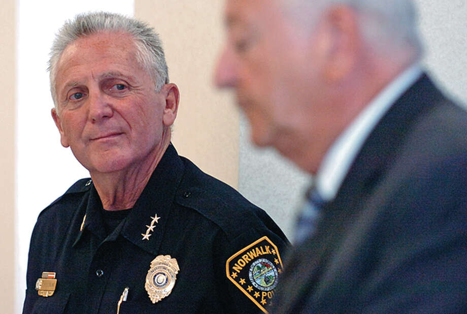 Norwalk Police Chief Harry Rilling listens to mayor Richard Moccia during a press conference where Rilling announced his retirement at Police HQ Thursday. / (C)2012, The Hour Newspapers, all rights reserved