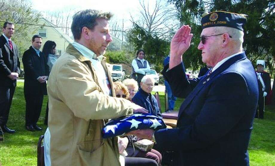 Hour photo / Alex von Kleydorff U.S. Army Spc. David Fahey Jr.''s uncle Michael Standeiner releases the folded U.S. flag to Sgt.-at-Arms Bobby Forbis during a ceremony to honor the fallen soldier. It will fly above American Legion Post 12 for 30 days.