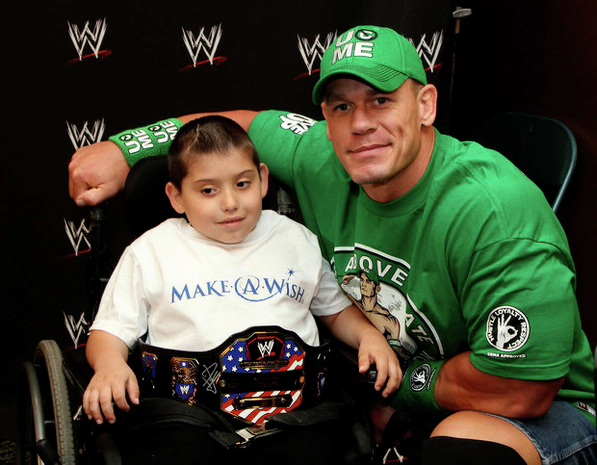 In this Monday, June 18, 2012 photo, seven-year old, Jonny Littman, poses with WWE superstar, John Cena, at the 300th Make-A-Wish for Cena in Uniondale, N.Y. It was the 300th wish granted by Cena, making him the most popular celebrity granter in Make-A-Wish history. (AP Photo/John Carucci)