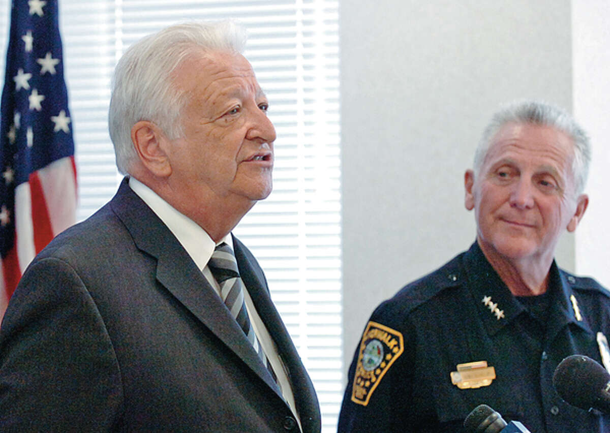 Norwalk Police Chief Harry Rilling listens to mayor Richard Moccia during a press conference where Rilling announced his retirement at Police HQ Thursday.
