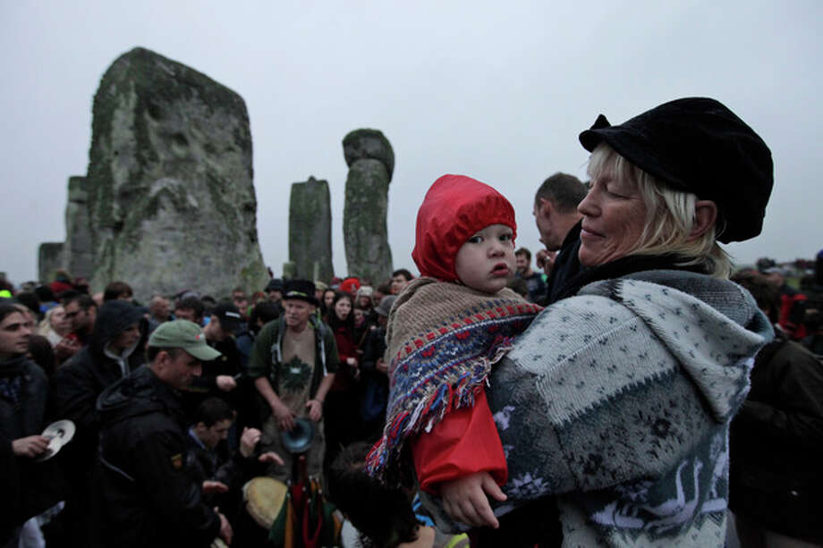 People gather during the summer solstice at Stonehenge, near Salisbury Thursday, June 21, 2012. Rain-sodden crowds welcomed a spectacularly rainy summer solstice at Stonehenge in true British fashion Thursday: With stoicism and wit. But through the wind and rain, drummers inside the ancient stone circle kept up their thumping rhythm, new age pagans kept up their chaotic dance, and visitors kept up their sense of humor. (AP Photo/Lefteris Pitarakis) / AP