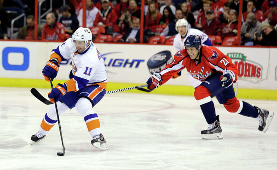 New York Islanders defenseman Lubomir Visnovsky (11), from Slovakia, looks to pass as Washington Capitals center Brooks Laich (21) reaches to defend during the first period of an NHL hockey game Tuesday, March 26, 2013, in Washington. (AP Photo/Alex Brandon) / AP