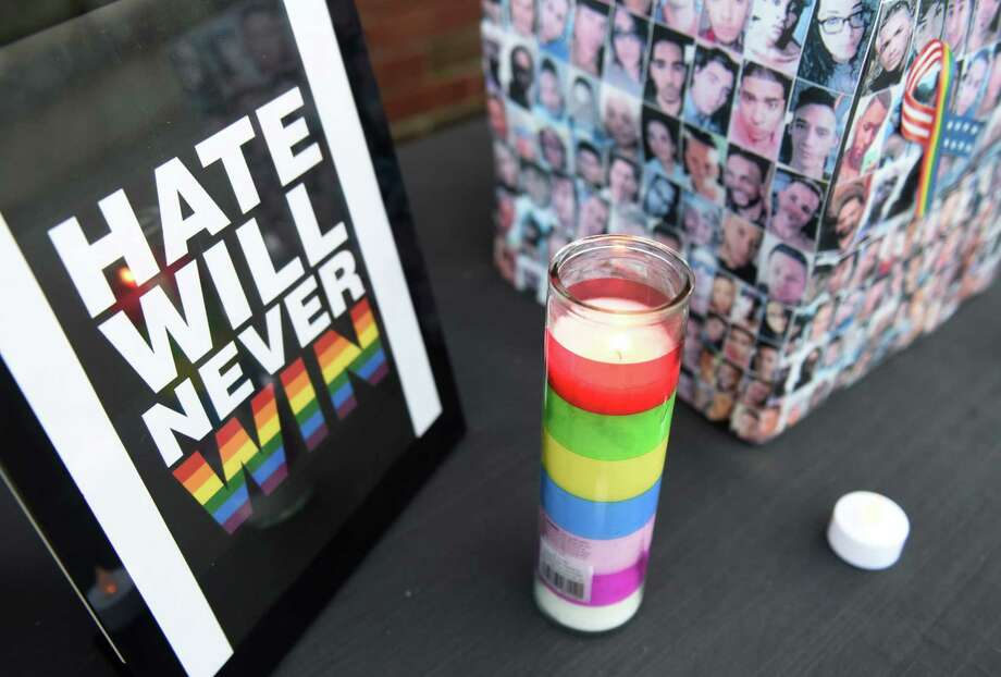 "A sign reading ""Hate will never win"" and a donation box with photos of the victims of the Orlando nightclub shooting sit on a table before the candlelight vigil held at local gay bar the Trevi Lounge in Fairfield, Conn. Tuesday, June 14, 2016. More than 100 folks gathered to mourn the 49 victims with a candlelight vigil while singing songs and telling stories of LGBT courage. Photo: Tyler Sizemore, Hearst Connecticut Media / Greenwich Time"