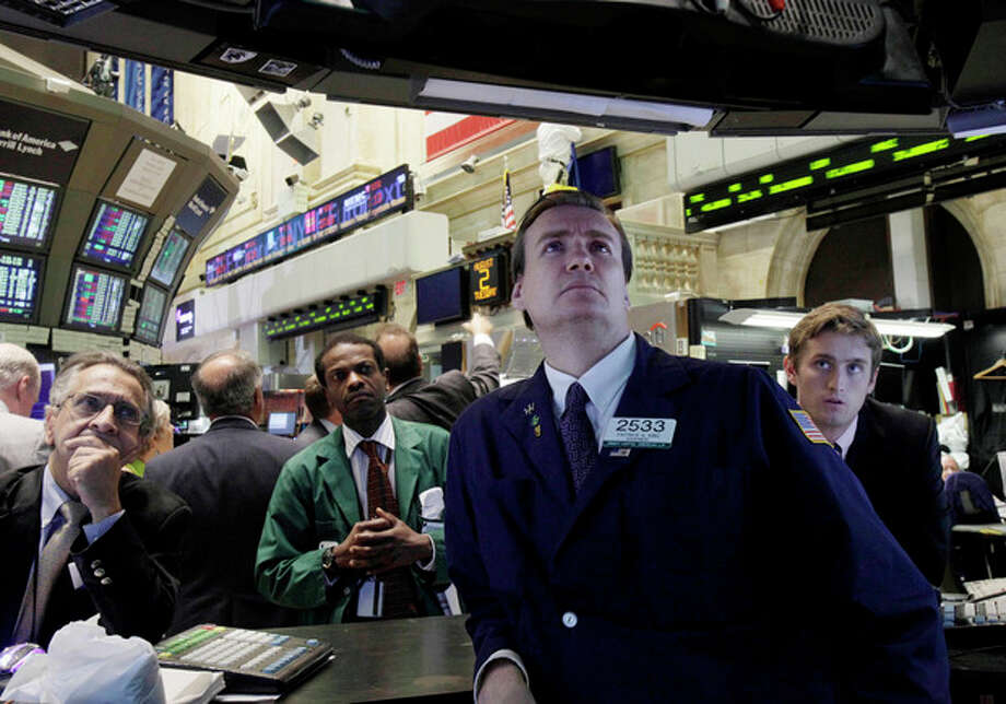 AP Photo/Richard Drew, File In this Aug. 2, 2011 file photo, specialist Patrick King, second from right, and others watch President Barack Obama's remarks on a television monitor the floor of the New York Stock Exchange. / AP2011
