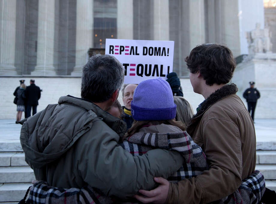 """A woman holds up a sign that reads """"REPEAL DOMA,"""" the Defense of Marriage Act, as a group from Alabama prays in front of the Supreme Court in Washington, Wednesday, March 27, 2013. In the second of back-to-back gay marriage case, the Supreme Court is turning to a constitutional challenge to the law that prevents legally married gay Americans from collecting federal benefits generally available to straight married couples. (AP Photo/Carolyn Kaster) / AP"""