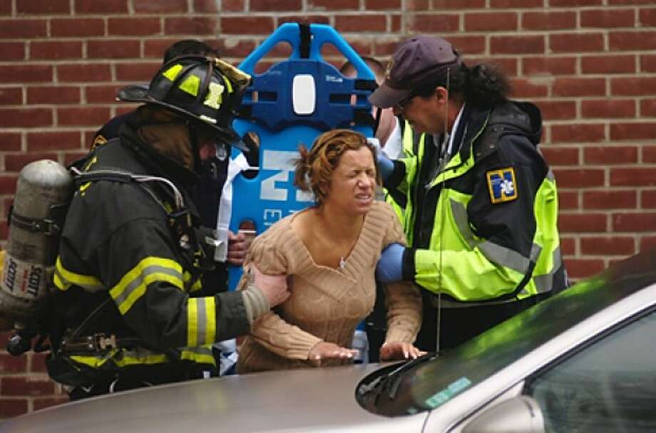 A woman is helped onto a backboard after she jumps from her second story window when smoke from a cooking fire filled her apartment building on Strawberry Hill Ave Wednesday morning. Hour photo / Erik Trautmann