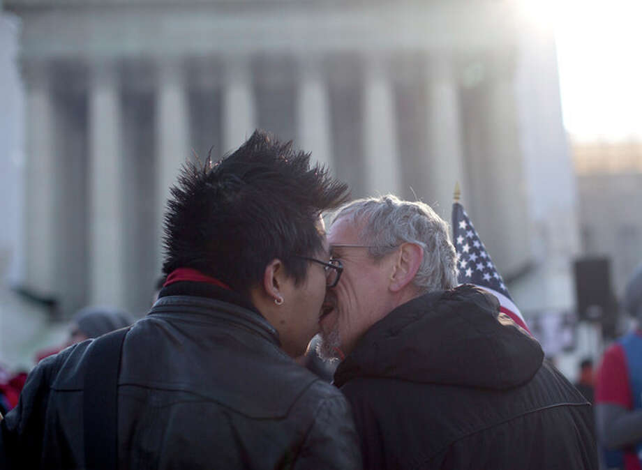 AP Photo/Carolyn KasterWyatt Tan, left and Mark Nomadiou, both of New York City, kiss in front of the Supreme Court in Washington, Wednesday, March 27, prior to the start of a court hearing on the 1996 Defense of Marriage Act (DOMA). In the second of back-to-back gay marriage cases, the Supreme Court is turning to a constitutional challenge to the law that prevents legally married gay Americans from collecting federal benefits generally available to straight married couples. / AP