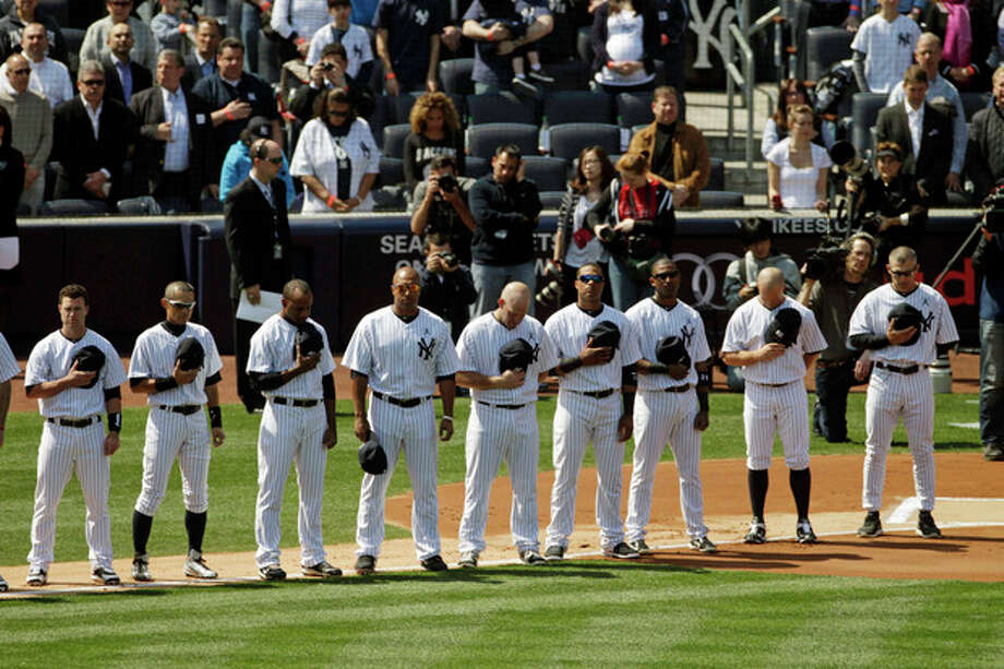 New York Yankees bow their heads during a moment of silence in honor of those killed in Newtown, Conn. before an opening day baseball game against the Boston Red Sox at Yankee Stadium, Monday, April 1, 2013 in New York. (AP Photo/Mark Lennihan) / AP