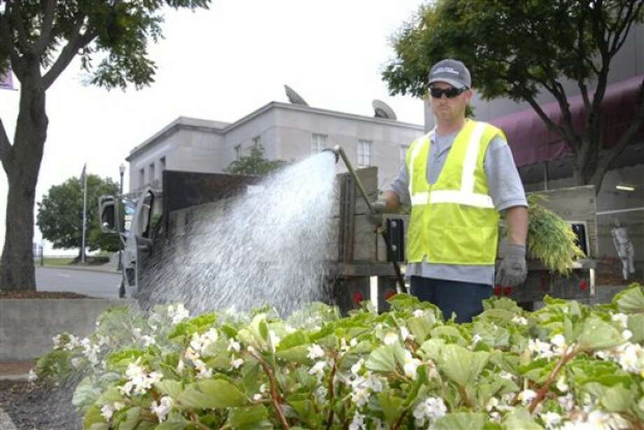 Chris Miller, with the City of Johnson City''s Landscaping Dept., spent the day watering/fertilizing the planters downtown, a process that must be done every other day during the hot weather, Tuesday, June 7, 2011. (AP Photo/The Johnson City Press, Lee Talbert)