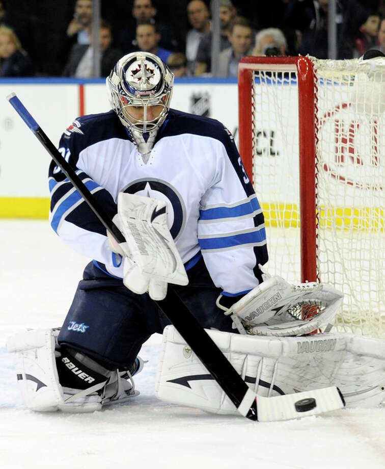 Winnipeg Jets goaltender Ondrej Pavalec deflects the puck during the second period of an NHL hockey game against the New York Rangers on Monday, April 1, 2013, at Madison Square Garden in New York. (AP Photo/Bill Kostroun) / FR51951 AP