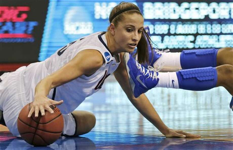 Connecticut guard Caroline Doty, left, tries to regain possession of the ball after colliding with Kentucky guard Janee Thompson, right, in the first half of a women's NCAA regional final basketball game in Bridgeport, Conn., Monday, April 1, 2013. (AP Photo/Charles Krupa) / AP