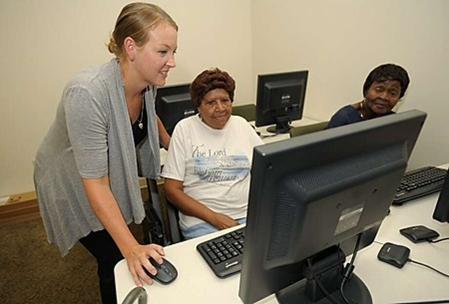 Family Self-Suffiency Program Director for Charter Oak Communities, Jessica Herlihy, chats with Post House residents Leora Shepard and Polly Williams in the building''s computer lab. The program offers residents onsite job counseling and training as well as job search opportunities. Hour photo / Erik Trautmann