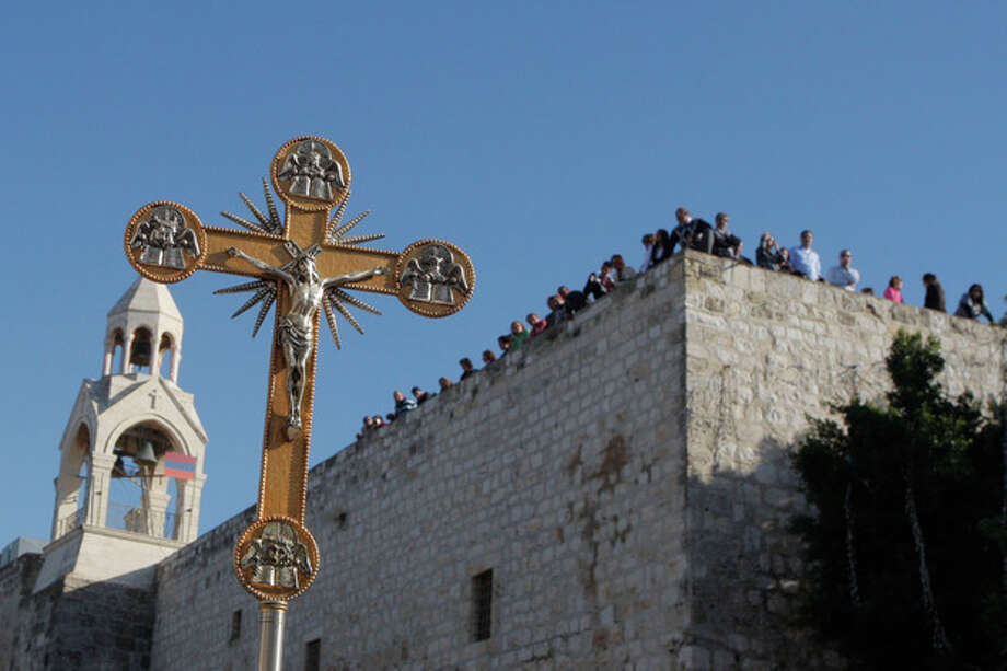 In this Friday, Dec. 24, 2010 file photo, a cross is seen backdropped by the Church of Nativity, traditionally believed by Christians to be the birthplace of Jesus Christ, during a Christmas parade in the West Bank town of Bethlehem. The Church of the Nativity in Bethlehem is becoming the church of contention with an unwelcome bid by the Palestinians to use their muscle as the newest members of the U.N.'s cultural arm and obtain World Heritage status for the iconic Christian site (AP Photo/Nasser Shiyoukhi, File) / AP