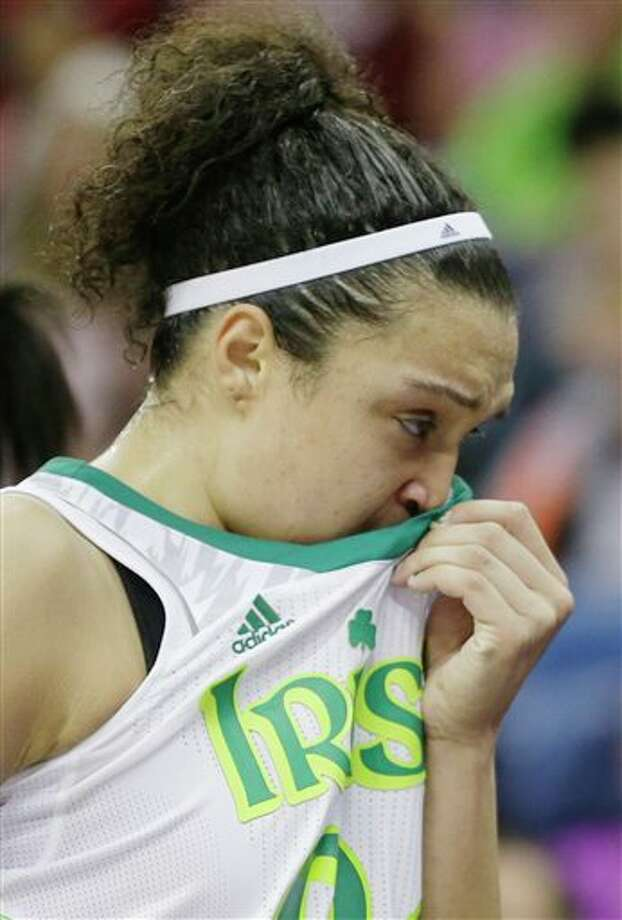 Notre Dame guard Kayla McBride (21) wipes her face in the second half of the women's NCAA Final Four college basketball tournament semifinal against Connecticut, Sunday, April 7, 2013, in New Orleans. UConn won 83-65. (AP Photo/Gerald Herbert) / AP2013