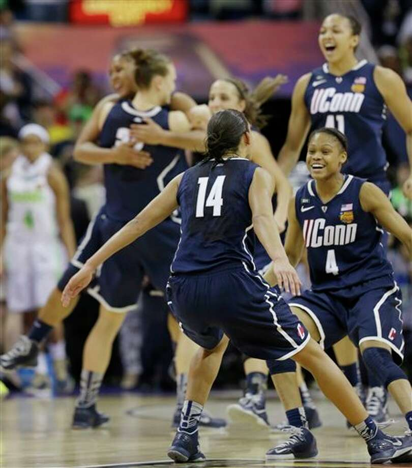 Connecticut players celebrate in the women's NCAA Final Four college basketball tournament semifinal against Notre Dame, Sunday, April 7, 2013, in New Orleans. UConn won 83-65. (AP Photo/Dave Martin) / AP2013