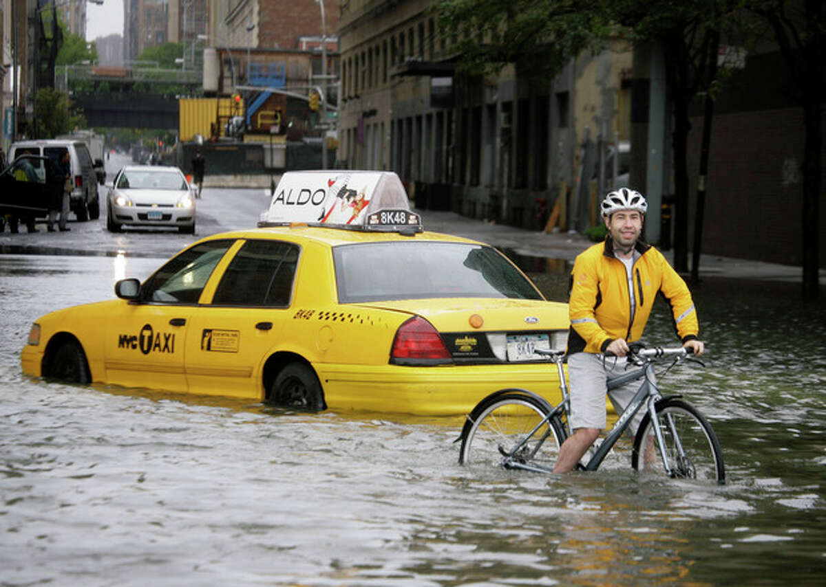FILE - In this Aug. 28, 2011 file photo, a bicyclist makes his way past a stranded taxi on a flooded New York City street as Tropical Storm Irene passes through the city. From Cape Hatteras, N.C., to just north of Boston, sea levels are rising much faster than they are around the globe, putting one of the world's most costly coasts in danger of flooding, according to a new study published Sunday, June 24, 2012, in the journal Nature Climate Change. By the year 2100, scientists and computer models estimate that sea levels globally could rise as much as 3.3 feet. The accelerated rate along the East Coast could add about another 8 to 11 inches, Asbury Sallenger Jr., an oceanographer for the USGS said.