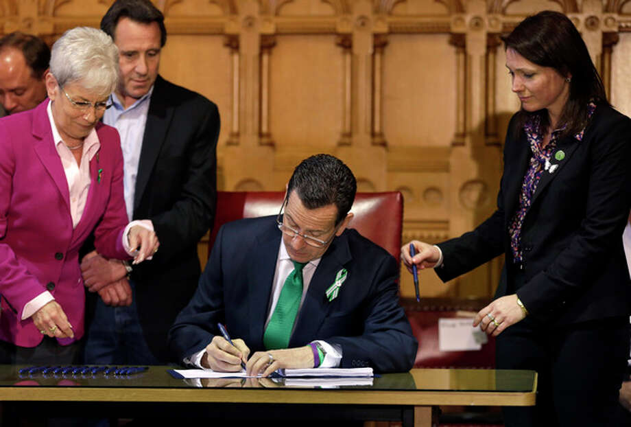 In this April 4, 2013, photo, Connecticut Gov. Dannel P. Malloy, center, signs legislation at the Capitol in Hartford, Conn., that includes new restrictions on weapons and large capacity ammunition magazines, a response to last year's deadly school shooting in Newtown. Neil Heslin, behind left, father of Sandy Hook shooting victim Jesse Lewis, Nicole Hockley, right, mother of Sandy Hook School shooting victim Dylan, and Conn. Lt. Gov. Nancy Wyman, left, watch. (AP Photo/Steven Senne) / AP