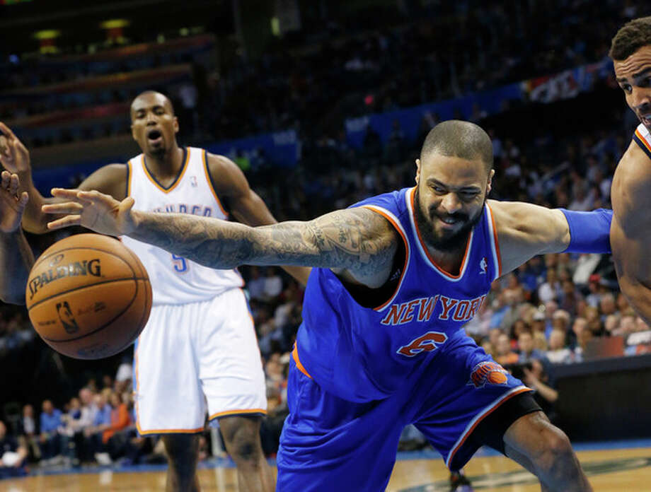 New York Knicks center Tyson Chandler (6) reaches for the ball after it was knocked away by Oklahoma City Thunder guard Thabo Sefolosha, right, in the first quarter of an NBA basketball game in Oklahoma City Sunday April 7, 2013. (AP Photo/Sue Ogrocki) / AP