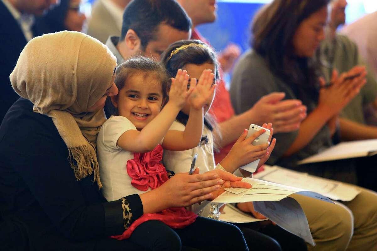 Sara Ali, 3, claps as her parents Mohammad and Aden are sworn in as U.S. citizens during a naturalization ceremony at Seattle City Hall, Tuesday, June 14, 2016.