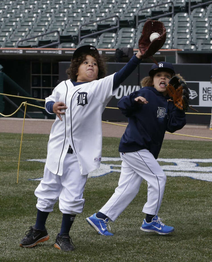 Jadyn, left, and Haven Fielder, sons of Detroit Tigers first baseman Prince Fielder play on the field before a baseball game between the Tigers and the New York Yankees in Detroit Sunday April 7, 2013. (AP Photo/Carlos Osorio)
