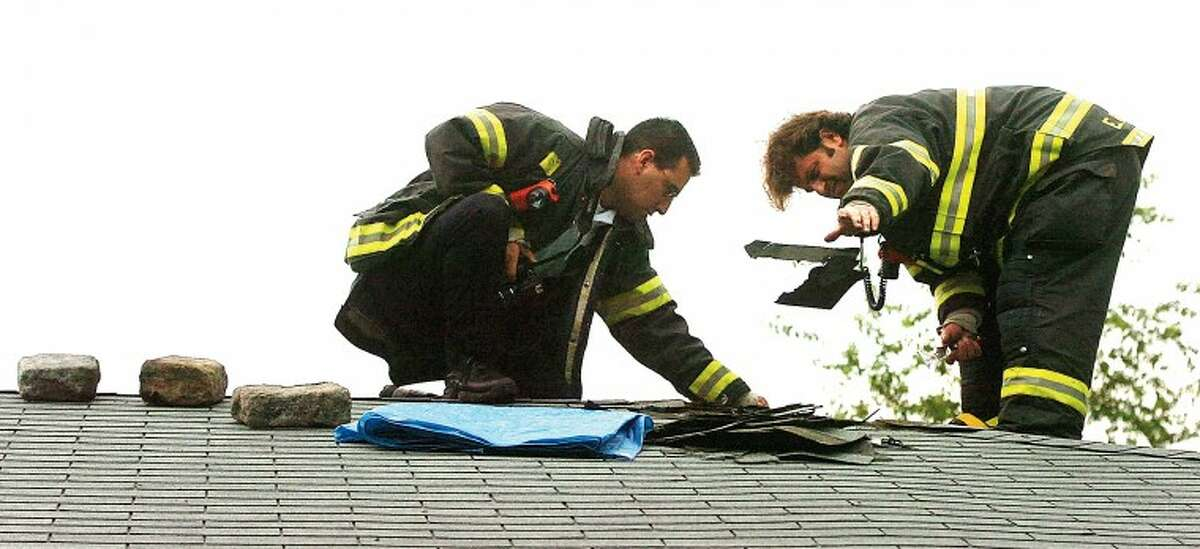 Hour Photo/ Alex von Kleydorff. Norwalk firfighters remove roofing tiles from an area around a hole of an Old Saugatuck Ave house that was hit by lightning during severe weather Monday morning