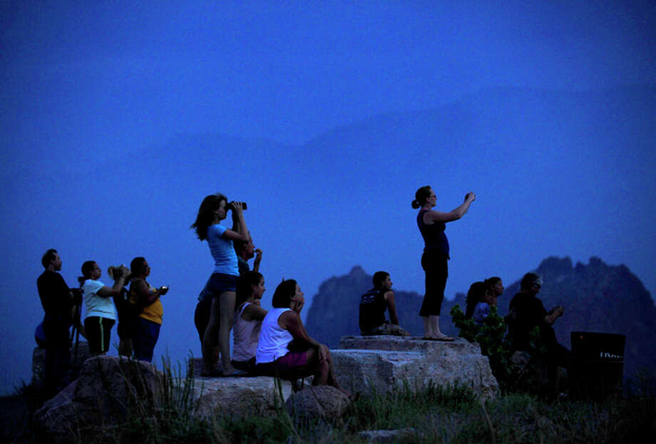 People watch from Mesa Road as a wildfire continues to burn west of Colorado Springs, Colo. on Sunday, June 24, 2012. The fire erupted Saturday and grew out of control to more than 3 square miles early Sunday, prompting the evacuation of more than 11,000 residents and an unknown number of tourists. (AP Photo/The Colorado Springs Gazette, Susannah Kay) / The Colorado Springs Gazette